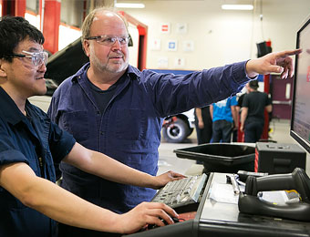 Automotive: Faculty and student working at diagnostic computer.