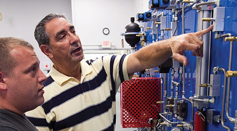 Manufacturing Technician Certificate: Manufacturing Technician certificate faculty and student discuss equipment.