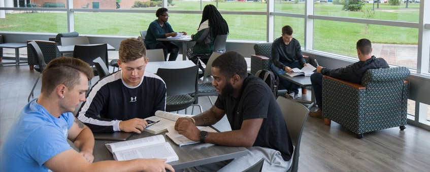 Students discuss coursework in a student lounge.