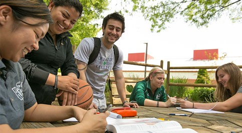 Students interacting outside on picnic table