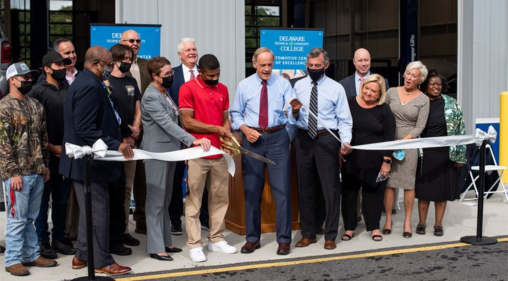 Senator Tom Carper and Automotive Technology Student Ronald Graham cutting the ribbon for the new facility surrounded by administrators, elected officials, and donors from the community