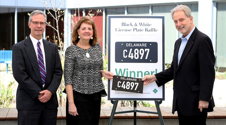 Winners of the black and white license plate raffle accepting the prize.