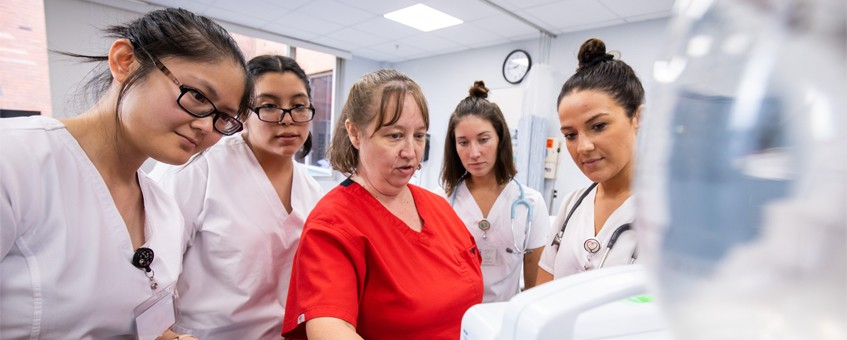A group of Nursing students surrounding their instructor while all look at a computer screen