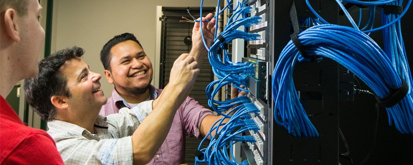 Two students and their instructor working on a server rack