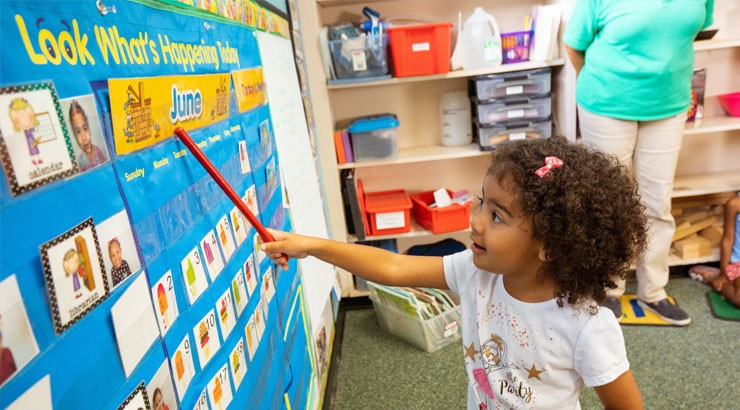 A student points at a calendar while at the child development center.