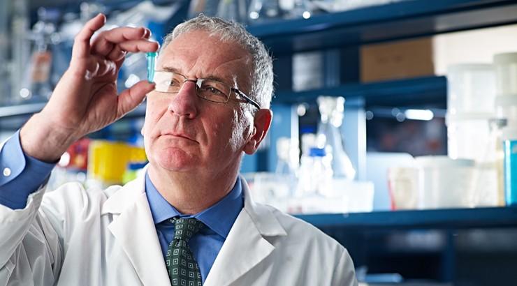 Scientist viewing a vial