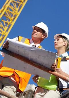 A surveyor and foreman on a job site.