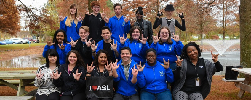 "Delaware Tech's American Sign Language club signing ""I love you"""