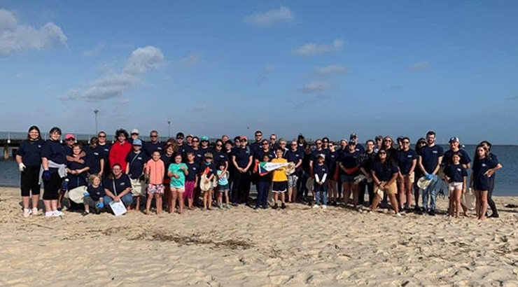 A large group of Coastal Cleanup volunteers posing together on a beach