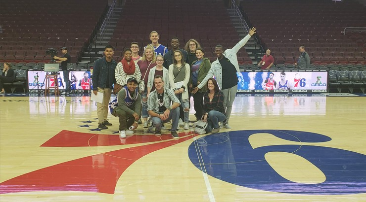Communications Students and Instructors sitting on the seventy sixers court