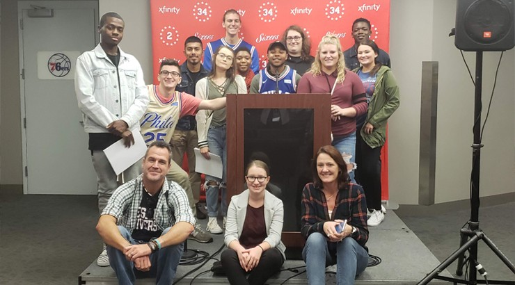 Communications Students and Instructors sitting in the seventy sixers press room