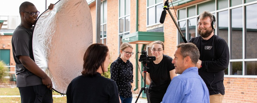 A group of students using filming equipment for an interview video