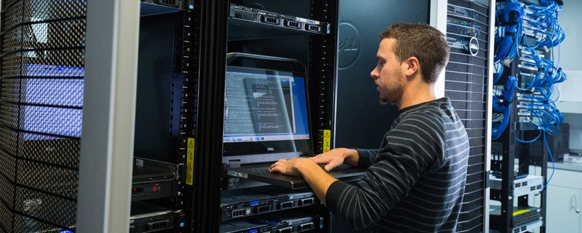 A computer engineering student working on a server in a server room