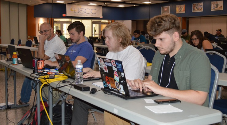 Bland Wallace III, Matthew Perrine, Samuel Hayden, and Kyle Bischof sitting at computers