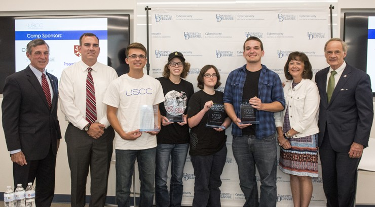 Students who participated in the Cyber Challenge standing with their awards alongside Governor John Carney and Senator Carper