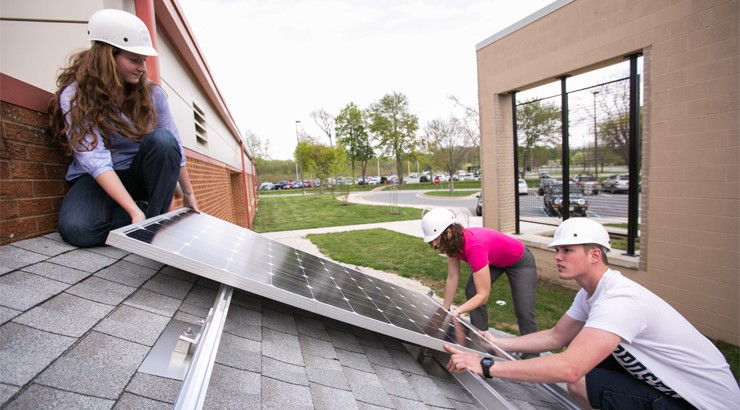 Three students in hard hats working on a solar panel
