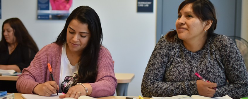 Two students in a Developmental Writing class in front of workbooks