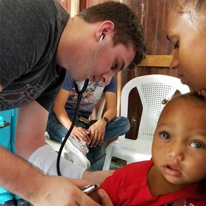A student using a stethoscope on a child in the Dominican Republic