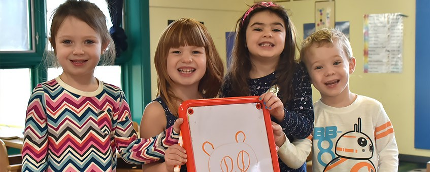 Four smiling children hold a whiteboard with a drawing on it.