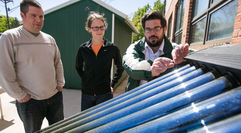 Energy program faculty discusses solar panel with students