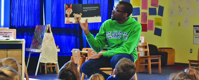 A student shows images from a book to a group of children as he reads in the classroom.