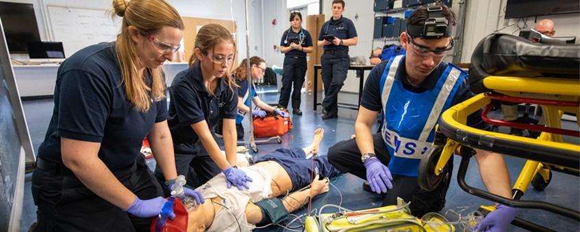 Emergency Medical Technician students practicing CPR on a test dummy