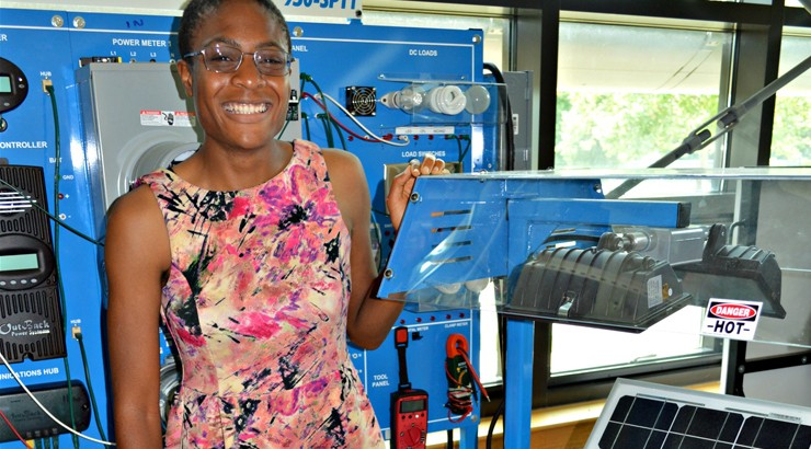Chidinma Emenike next to a portable solar panel training station in the College's energy lab