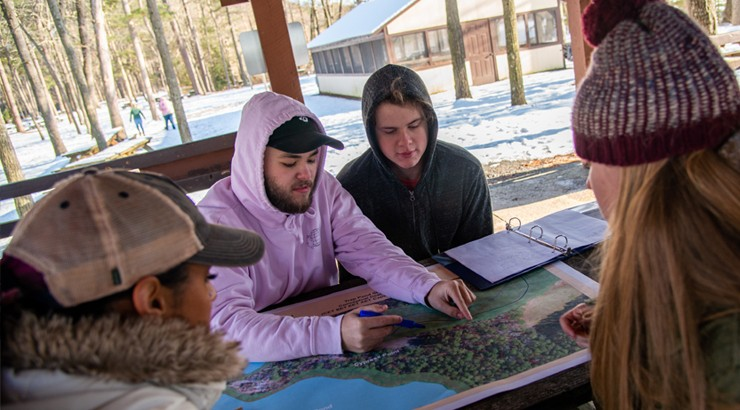 Students in the civil, environmental, and architectural engineering disciplines, from left, Siera Butler, Colby Kaczka, Eric Meding, and Ashley Melvin use a map to discuss options for site development