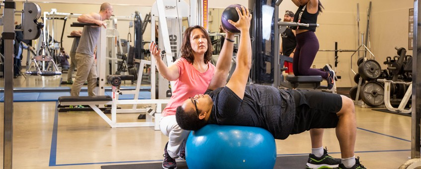 An exercise coach working with a student who is lifting weights on an exercise ball