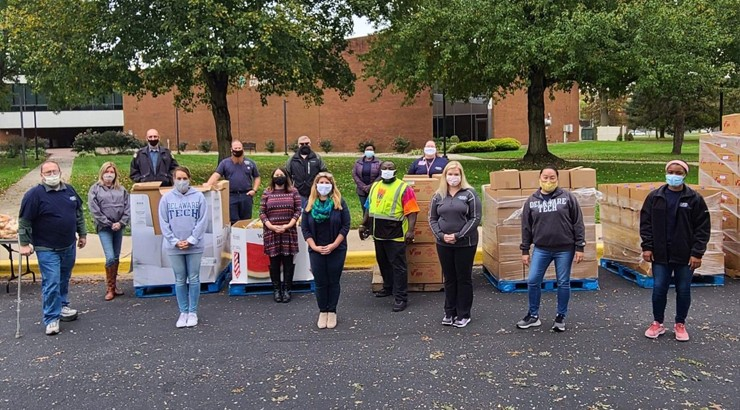 Volunteers in masks standing in front of food boxes in the Terry parking lot at the Dover campus
