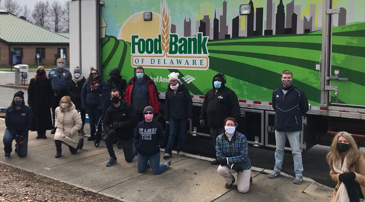 Volunteers in masks standing and kneeling in front of a Food Bank of Delaware truck at the Georgetown campus