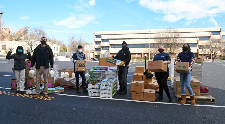 Volunteers in masks holding boxes in the Wilmington campus parking lot