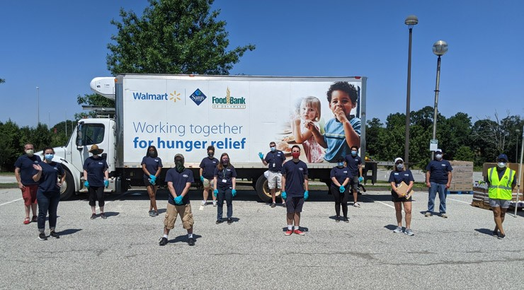Volunteers pose in front of the Food Bank distribution truck.