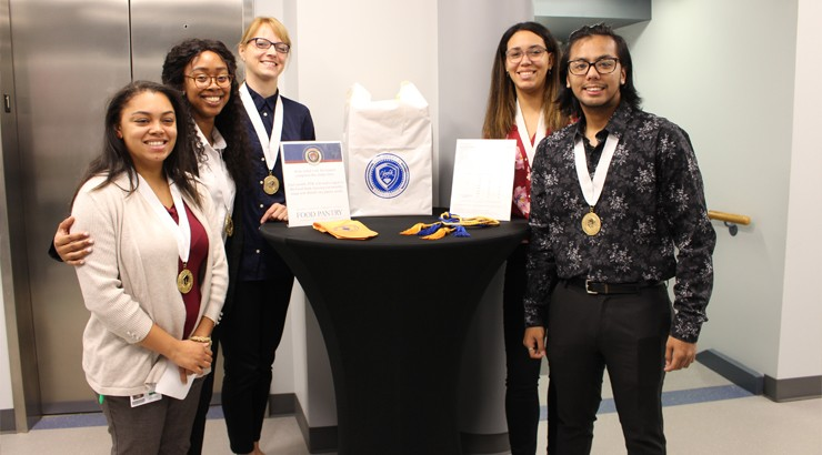 A group of students standing around a table wearing ornamental awards around their necks