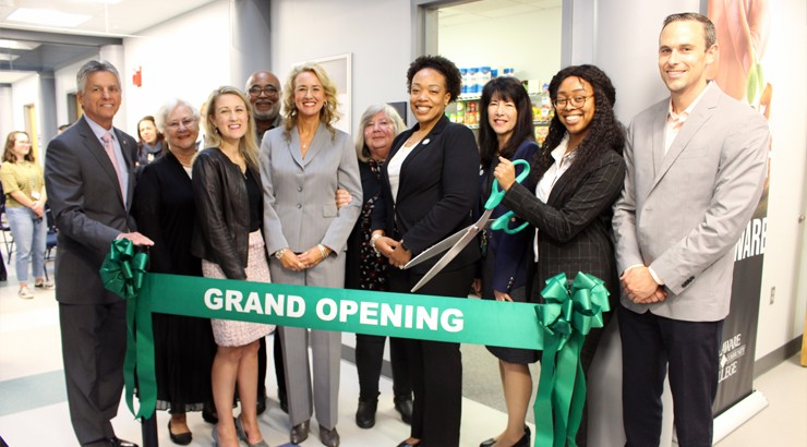 A group of people standing behind a large green ribbon that says Grand Opening in white text. One person is holding a pair of large green scissors to cut the ribbon with.