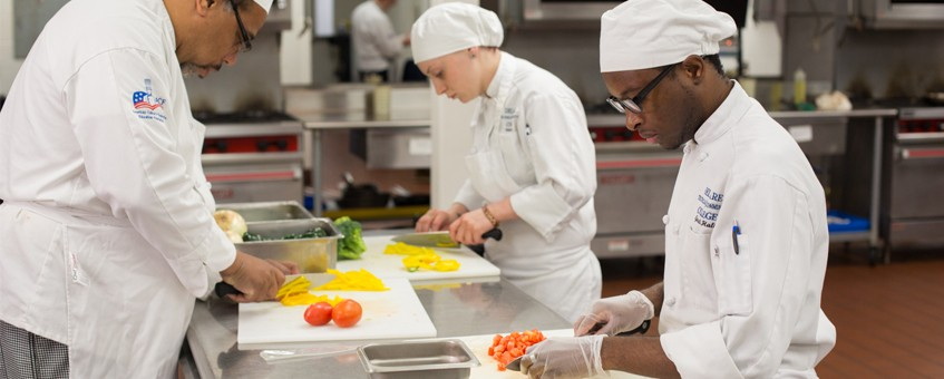 Three students preparing ingredients in a kitchen
