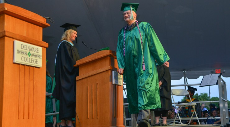 Frederick Paul Reich walking across the stage at graduation in his cap and gown