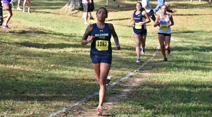 Cortez running at a Cross Country meet with two runners in the background behind her