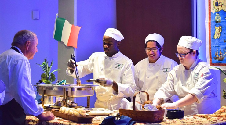 Three culinary students serving a Gala attendee