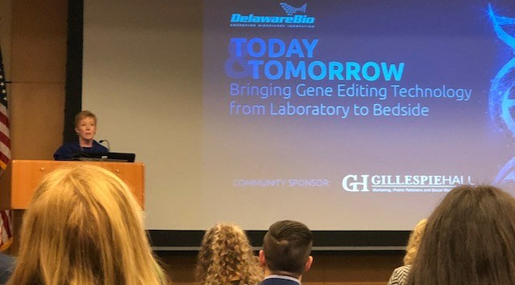 A presenter at the symposium displaying a slide presentation with the words Today and Tomorrow Bringing Gene Editing Technology from Laboratory to Bedside