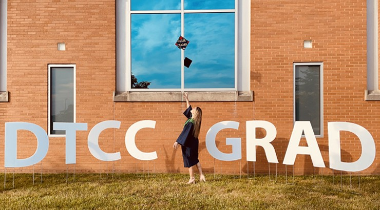 Delaware Tech student Joanna Baker standing in her graduation regalia between large white letter signs that spell out DTCC Grad. She is throwing her graduation cap in the air and on the cap is decorative text that says Future Teacher.