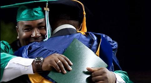 Two graduates hug.