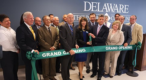 Group cutting ribbon at grand opening