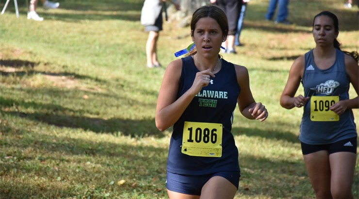 Hannah Walker running in a Cross Country meet with the number 1086 pinned to her jersey and a fellow runner in the background