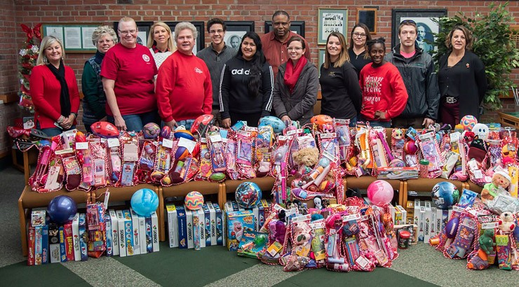 Alpha Beta Gamma (ABG) students and advisors stand in front of toys collected to donate to the Salvation Army.