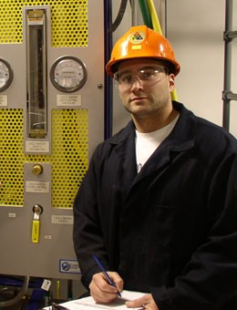 Student chemical operator with hardhat in field