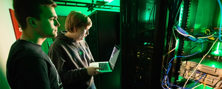 Two Information Technology and Networking students working in a server room