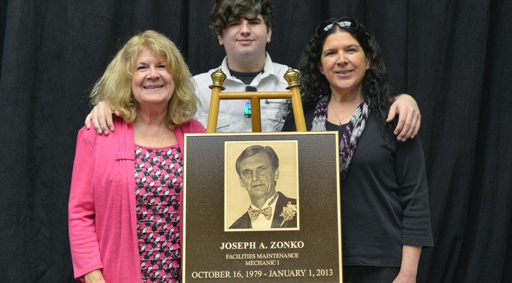 Family members of Joseph Zonko stand behind the plaque