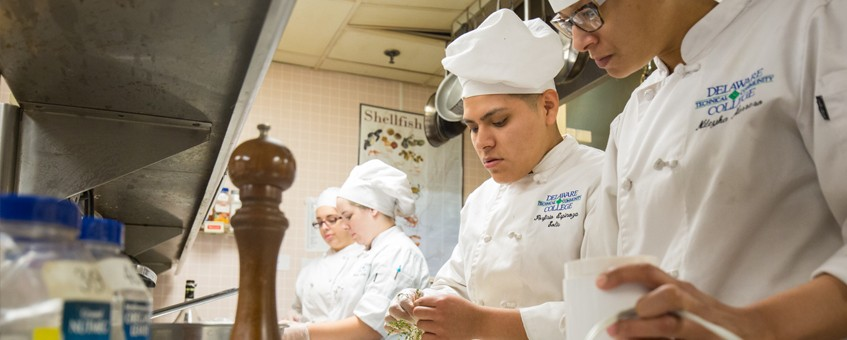 Culinary students working through an assignment in their culinary uniforms at the Stanton campus