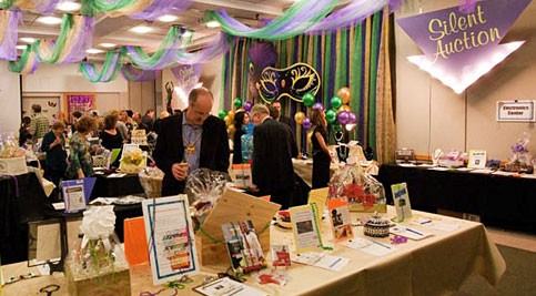 Mardi Gras guests peruse the silent auction items.